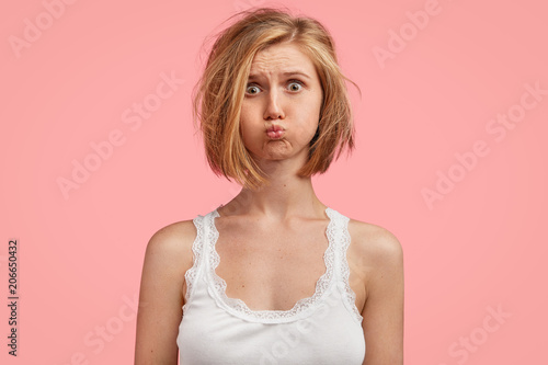Fotografía Beautiful female adult blows cheeks, has sleepy expression, fed up of morning routine, wants to have holidays, dressed in casual white pyjamass, isolated on pink background