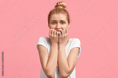 Fotografía  Anxious nervous blonde woman bites finger nails with anxiety, feels worried before being operated, wears casual white t shirt, poses against pink background