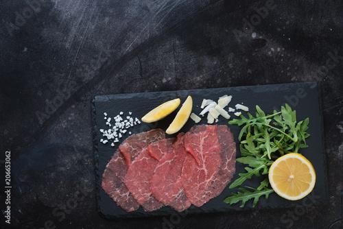 Stone slate with carpaccio beef, arugula, lemon and parmesan Wallpaper Mural