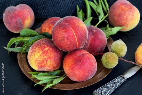 Photo  reife und unreife Pfirsiche auf einem Kupferteller mit Obstmesser