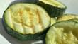 BBQ zucchini rotates on white plate. Super macro view