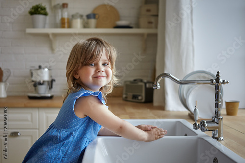 6a70ebb2878a Charming little girl in blue dress washing hands in kitchen. Cute female  kid looking and