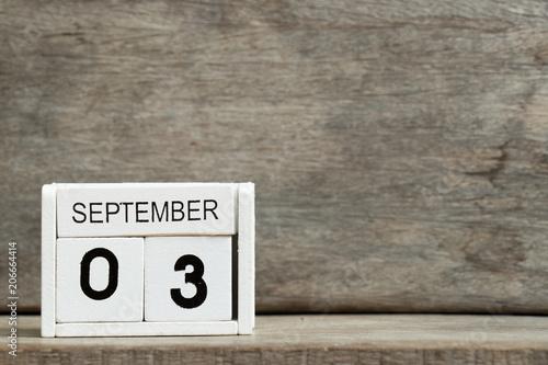 Fényképezés  White block calendar present date 3 and month September on wood background