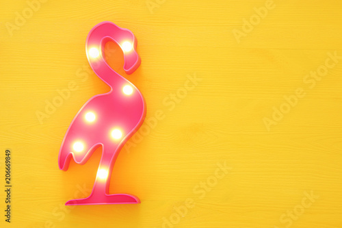 Fototapeta  a plastic flamingo lamp with leds over yellow wooden background
