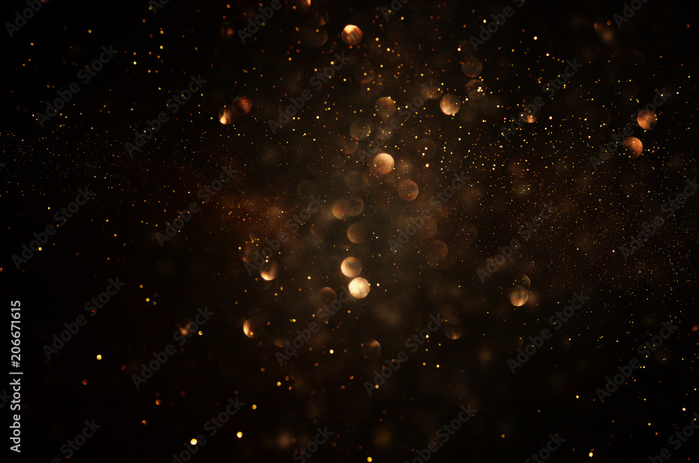 glitter vintage lights background. dark gold and black. de focused.