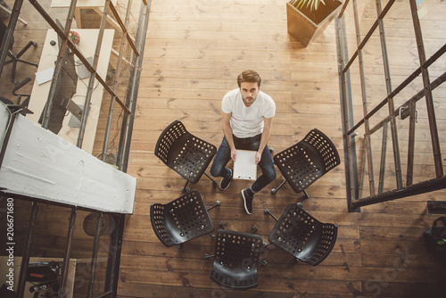 Fotografía  Top view full length portrait of serene male looking at camera while sitting nea