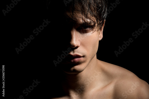 Cuadros en Lienzo Close up portrait of young mysterious guy with half face in shadow