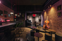Modern Jazz Bar Interior Design, Stage With Black Piano And Cello, Lamps Above Bar Counter