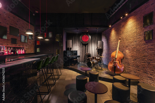Modern jazz bar interior design, stage with black piano and cello, lamps above b Lerretsbilde