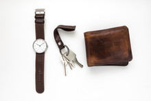 Top View Of Everyday Carry Objects Made By Brown Leather Wrist Watch, Key Chain, Wallet On White Background