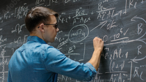 Photo Brilliant Young Mathematician Approaches Big Blackboard and Finishes writing Sophisticated Mathematical Formula/ Equation