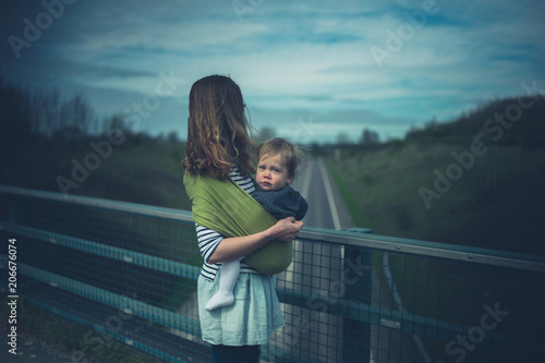 Fotografia, Obraz  Young mother with baby on road bridge