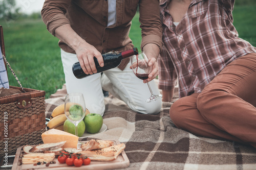 Foto op Plexiglas Picknick Close up of man arm pouring red wine from bottle into glass. Woman is sitting near husband on the blanket and relaxing. Romantic picnic on grass field concept