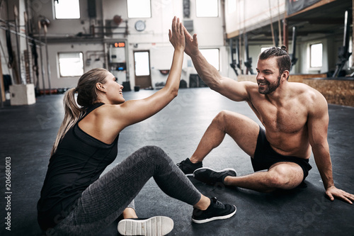 Fotografía  Two fit young people high fiving together after a workout