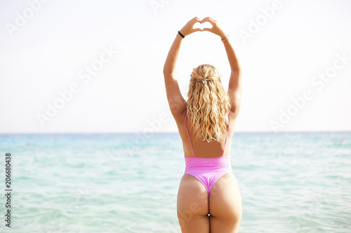 Fototapeta Woman back sexy butt portrait doing heart shape gesture in front of the sea obraz na płótnie
