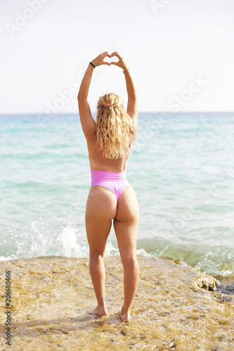 Fototapeta Sexy romantic young blond woman making a heart gesture with her fingers in with sea view obraz na płótnie