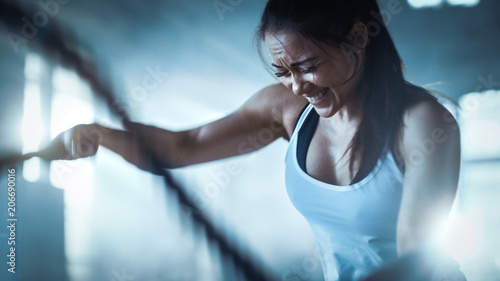 Poster Fitness Athletic Female in a Gym Exercises with Battle Ropes During Her Cross Fitness Workout/ High-Intensity Interval Training. She's Muscular and Sweaty, Gym is in Industrial Building.