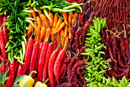 Photo Stands Hot chili peppers Heap Of Ripe Big Red Peppers At A Street Market In thailand
