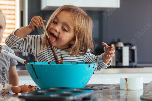 Girl licking chocolate cream while baking