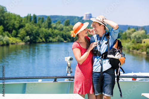 Fotografia Happy couple on river cruise wearing sun hats in summer