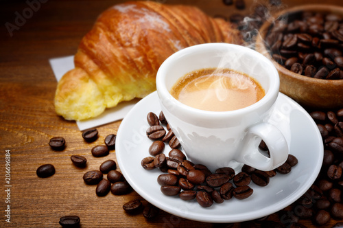 Fototapeta Espresso and croissant with coffee beans on wood background obraz