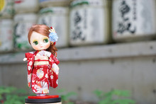 Cute Doll In Kimono. A Cute Doll Is Dressing Up In A Red Kimono. Kimono Is A Traditional Japanese Garment. The Doll Is Standing In Japanese Setting. Background Is Abstract Blur Of Japanese Sake Barrel