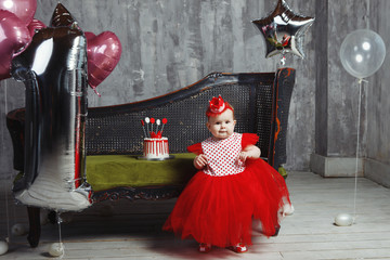 Child girl in a bright red dress, in a hat, on a vintage sofa in the studio in a room with cake and ballons with grey background.