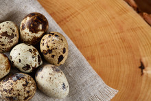Quail Eggs Arranged In Circle On A Napkin On A Log Over A Wooden Background, Close-up, Selective Focus.