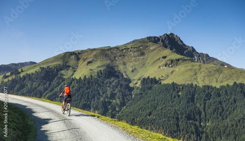 Fotografie, Obraz  senior woman underway on her electrical mountain bike to the summit of Kitzbuehl