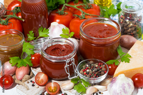 Fotobehang Kruiderij tomato sauces, pasta and fresh ingredients on wooden background