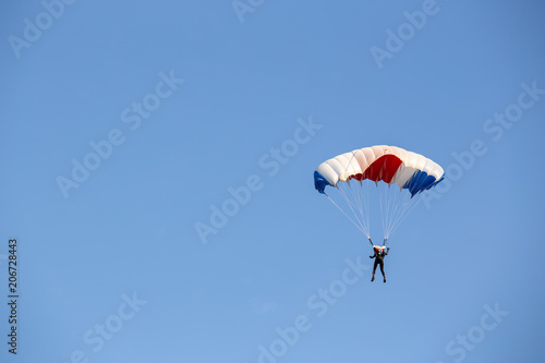 Papiers peints Aerien isolated skydiver control colorful parachute gliding after free fall jump with blue sky background