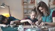 a young mother with two small daughters is engaged in creativity in a home workshop. children make crafts out of clay