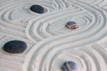 Fototapeta na wymiar Pyramids of gray zen stones on light sand. Concept of harmony, balance and meditation, spa, massage, relax
