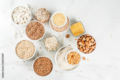 Fotomural Selection various types cereal grains groats  in different bowl on white marble