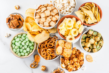 Variation different unhealthy snacks crackers, sweet salted popcorn, tortilla...