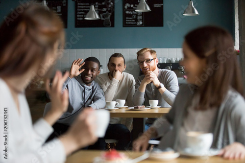 Платно African smiling millennial man waving hand saying hello greeting young women mee
