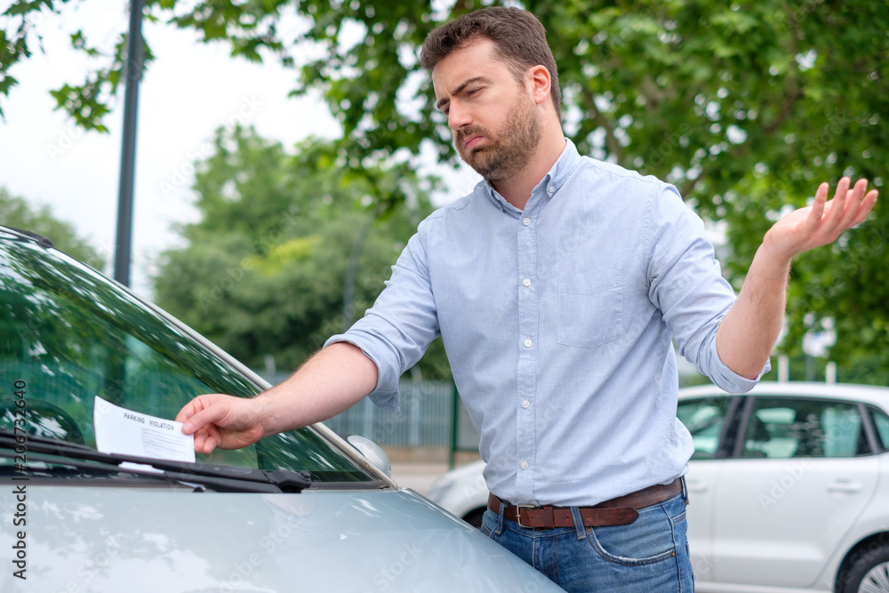Fototapety, obrazy: Angry man looking on parking ticket placed under windshield wiper