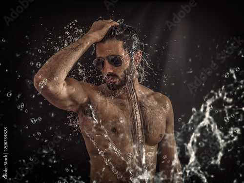 Fotografia  Shirtless handsome young man with water splashes on his face and chest in studio