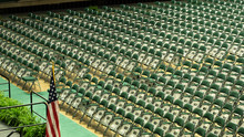 Multiple Green Chairs Arranged In Front Of Stage With American Flag