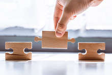 Hand Holding A Wooden Jigsaw Puzzle With Blank Space. There Is A Matching Puzzle Next To It. The Concept Of Solving Problems, All Problems Can Be Solved, Connection.