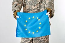 Mannequin In Military Army Uniform Holding European Flag. White Isolated Background.