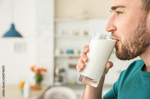 Young man drinking tasty milk at home