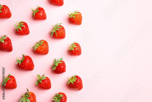 Flat lay composition with with tasty ripe strawberries on color background