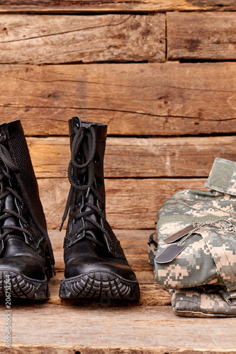 Fotografía  Black combat soldiers boots and clothes. Wooden desk background.