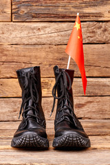 Pair of soldier army boots with flag of china. Wooden desk background.