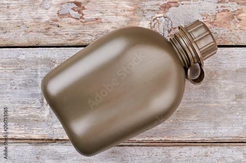 Fotografia  Army water bottle. Wooden desk background. Top view, flat lay.