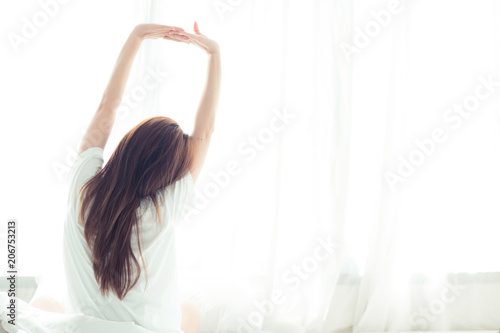 Fotografie, Obraz  Beautiful young asian woman stretch and relax in bed after wake up morning at bedroom, back view, new day and resting for wellness, lifestyle concept