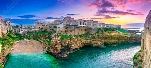 Polignano a Mare, Puglia, Italy: Sunset at Cala Paura gulf with Bastione di Santo Stefano and Lama Monachile beach in background, Apulia, Italy, province of Bari