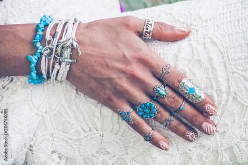 Photo  closeup of young woman hand with lot of boho style jewrly, rings and bracelets o