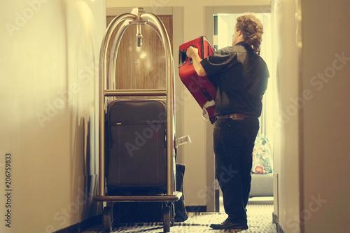 Zdjęcie XXL Zbliżenie wiele walizki na hotelowej bagaż furze kroczy dzwonkową chłopiec. Bagażowy portier lub dzwoneczek przynoszący walizkę gości z furgonetką do pokoju hotelowego. Bagaż na kółkach w hotelu. Tonowanie